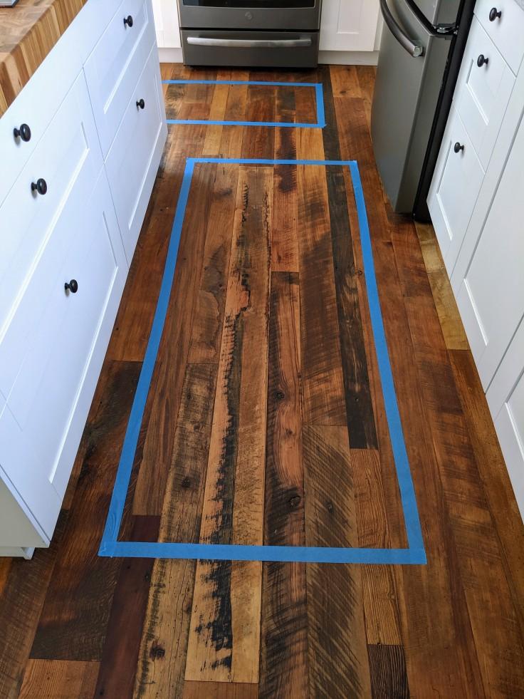 Panters tape on floor to mark placement of kichen floor mat