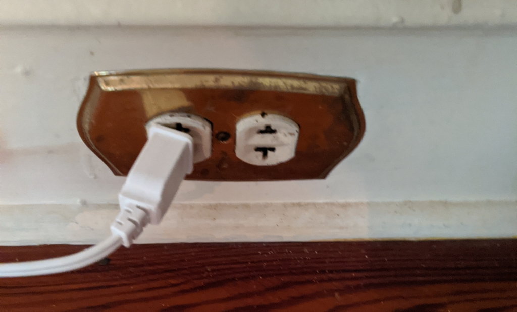 Two-pronged receptacle with brass face plate